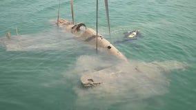 Opheffend van de bodem van het overzees een oud gevallen Duits vliegtuig vanuit de tijd van de Tweede Wereldoorlog stock videobeelden