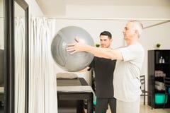 Opheffende de Oefeningsbal van fysiotherapeutassisting elderly man stock foto's