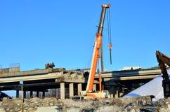 Opheffende mobiele kraan, die een grote gewapend beton plak, bouw ontmantelen van een automobiele brug bij een bouw stock foto