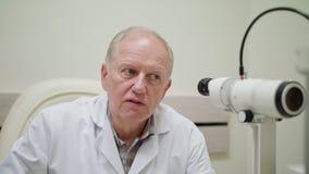 Ophtalmologist examina e Talkes ao paciente imagens de stock royalty free