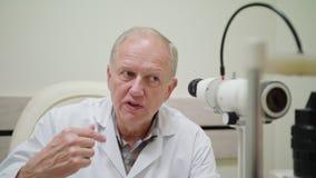 Ophtalmologist undersöker och Talkes till patienten arkivfilmer