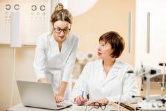 Ophtalmologue supérieure de femme avec le jeune assistant féminin dans le bureau Photo libre de droits