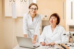 Ophtalmologue supérieure de femme avec le jeune assistant féminin dans le bureau Photos libres de droits