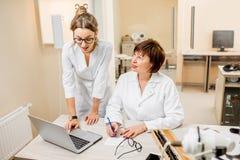 Ophtalmologue supérieure de femme avec le jeune assistant féminin dans le bureau Images libres de droits