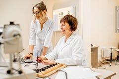 Ophtalmologue supérieure de femme avec le jeune assistant féminin dans le bureau Image stock