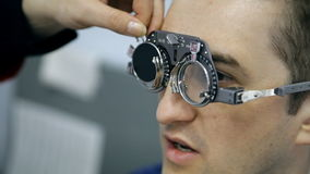 An ophthalmologist is checking a man's vision stock footage