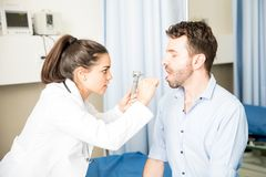 Ophthalmologist checking throat of a patient. Professional young doctor using wooden stick and otoscope to examine throat of sick male patient Stock Images