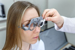 Ophthalmologist checks the eyes of a girl. Optometrist examining female patient in ophthalmology clinic Stock Images