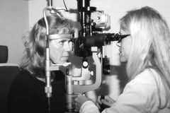 Ophthalmologist conducting an eye examination. Eye doctor performing a routine exam Royalty Free Stock Photography