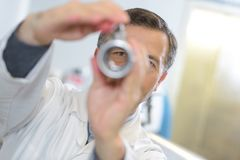 Ophthalmologist examines eyes with handheld lense Stock Image