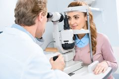 ophthalmologist examining female patient vision with slit lamp royalty free stock photography