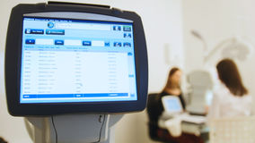 Ophthalmologist in eyes clinic doing diagnostic with vision of patient by modern computer systems - high technology Stock Photography