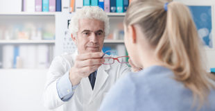 Ophthalmologist giving glasses to the patient Stock Images