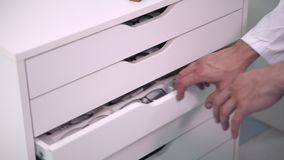 Ophthalmologist hands close up, choosing glasses from a drawer in the optical store. Ophthalmologist hands close up, choosing glasses from a drawer in the stock footage