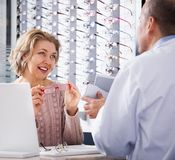 Ophthalmologist helping  pensioner to chose glasses. Ophthalmologist helping  female pensioner to chose new glasses Stock Photos