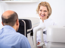 Ophthalmologist and male pensioner checking eyesight Stock Photo