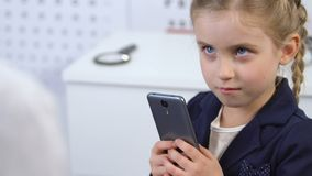 Ophthalmologist trying to take smartphone from girl hands, gadget addiction. Stock footage stock video footage