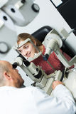 Ophthalmologist and woman checking eyesight. Senior male ophthalmologist and young women checking eyesight in clinic royalty free stock photography