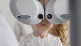 Ophthalmology clinic for children - adorable little blonde girl checks vision eyesight, close up. Telephoto stock photos