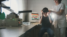 Ophthalmology doctor checks the boy`s vision with the help of stereovideo virtual reality glasses Royalty Free Stock Photos