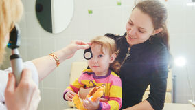 Ophthalmology - doctor checks eyesight at little girl - child`s healthcare Royalty Free Stock Photos