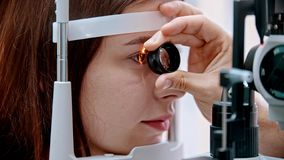 Free Ophthalmology Treatment - A Young Woman Checking Her Visual Acuity With A Light Of Special Big Optometry Machine And Royalty Free Stock Photography - 166865407