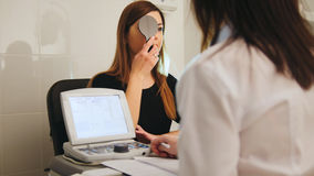 Ophthalmology - white woman checks vision in an ophthalmologist room - short-sighted and squints Royalty Free Stock Images