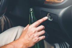 Opiły mężczyzna jedzie samochód na drogowej mienie butelki jazda po pijanemu piwnym Niebezpiecznym pojęciu fotografia stock
