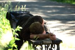 Opiły mężczyzny dosypianie w parku na drewnianej ławce obraz stock