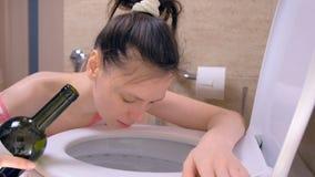Opiła kobieta wymiotuje w toaletowym obsiadaniu na podłodze z wino butelką w ręce w domu, ranek kac, boczny widok zdjęcie wideo