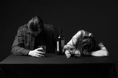 Opiła para, mężczyzna i kobieta, przeciekamy na stole, stalowy utrzymanie zdjęcie stock