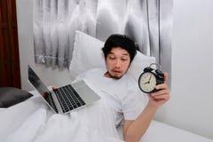 Opiły Azjatycki mężczyzna z laptopu, budzika łgarskim puszkiem na i zdjęcia royalty free