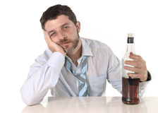 Opiły biznesowy mężczyzna marnotrawiący i whisky butelka w alkoholizmu fotografia royalty free