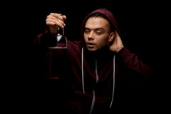 Opiły facet z butelką piwo Młoda alkoholiczka w czerwonym hoodie na czarnym tle Alkoholiczny nałogu pojęcie Zdjęcie Royalty Free