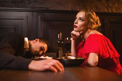 Opiły mężczyzna śpi przy stołem przeciw kobiecie obrazy stock