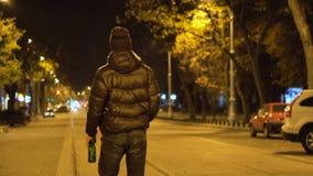 Opiły mężczyzna chodzi noc brukujący ulicznym i pijący piwo tworzy butelkę zdjęcie wideo