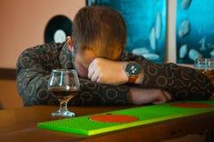 Opiły mężczyzna dosypianie przy baru stołem blisko szkła brandy Fotografia Stock