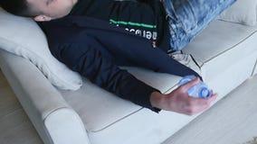 Opiły mężczyzna miejsca siedzące na kanapie Potomstwo pijący mężczyzna miejsca siedzące w żywym pokoju z butelką w jego ręce na k zbiory wideo