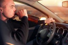Opiły młody człowiek jedzie samochód z piwną butelką obraz stock