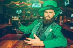 Opiły młody człowiek w zieleni St Patrick kostiumu siedzi przy stołem w pubie Trzyma kubek ciemny piwo Faceta chłodzić obrazy royalty free