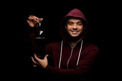 Opiły uczeń na czarnym tle Boozed, ładny facet pokazuje butelkę alkoholiczny napój, Ucznia partyjny pojęcie obraz royalty free
