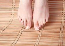 Opieka dla pięknej kobiety iść na piechotę na podłoga piękne nogi odosobnione tła nad białą kobietą Zdjęcie Royalty Free