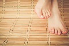 Opieka dla pięknej kobiety iść na piechotę na podłoga piękne nogi odosobnione tła nad białą kobietą Fotografia Stock
