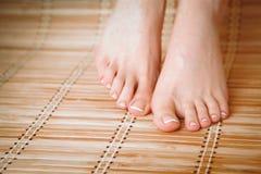 Opieka dla pięknej kobiety iść na piechotę na podłoga piękne nogi odosobnione tła nad białą kobietą Zdjęcia Stock
