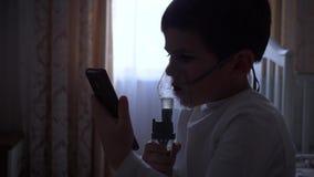 Opieka zdrowotna dziecko, chora chłopiec używa telefon komórkowego przez nebulizer z podczas gdy traktowania rozognienie drogi od zdjęcie wideo