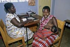 Opieka zdrowotna, Maasai matka breastfeeding w klinice Zdjęcie Stock