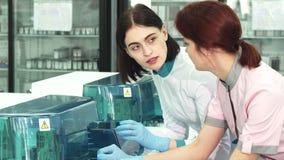 Opieka zdrowotna naukowowie dyskutuje analizujący maszynę przy lab obrazy royalty free