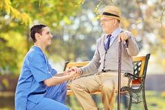 Opieka zdrowotna profesjonalista pomaga starszego mężczyzna obsiadaniu na ławce Obraz Stock