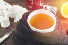 Opieka zdrowotna, tradycyjna medycyna i grypy pojęcie, - filiżanka herbata z cytryną, termometrem i lekami na drewnianym stole, zdjęcia royalty free