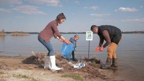 Opieki natury ekologia, rodzina wolontariuszi z małym synem czyści w górę klingerytu i polietylenu grat na brudnym nabrzeżu, zbiory